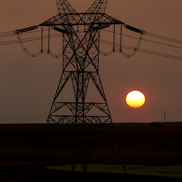 """Silhouette of large metal electrical tower with power lines and orange sun..."" stock image"