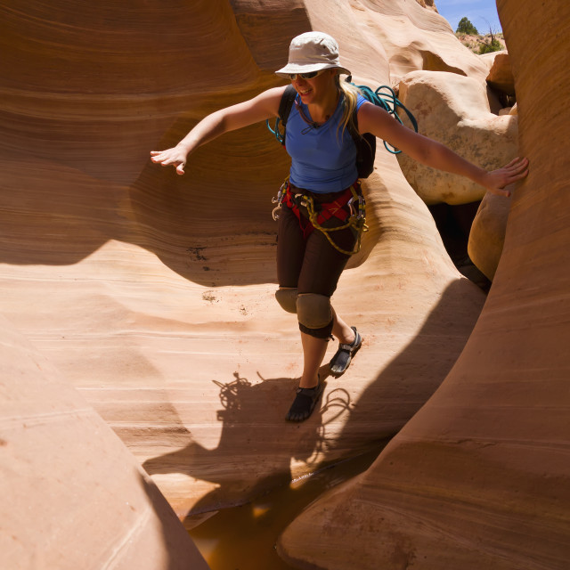"""Female athlete navigating a slot canyon water feature; Hanksville, Utah,..."" stock image"