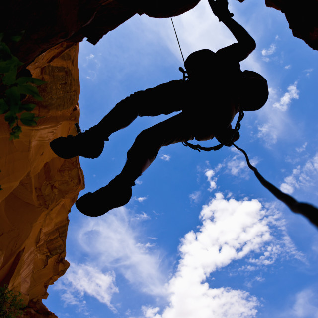 """Looking upwards to the silhouette of an adventurer rappelling down a canyon..."" stock image"