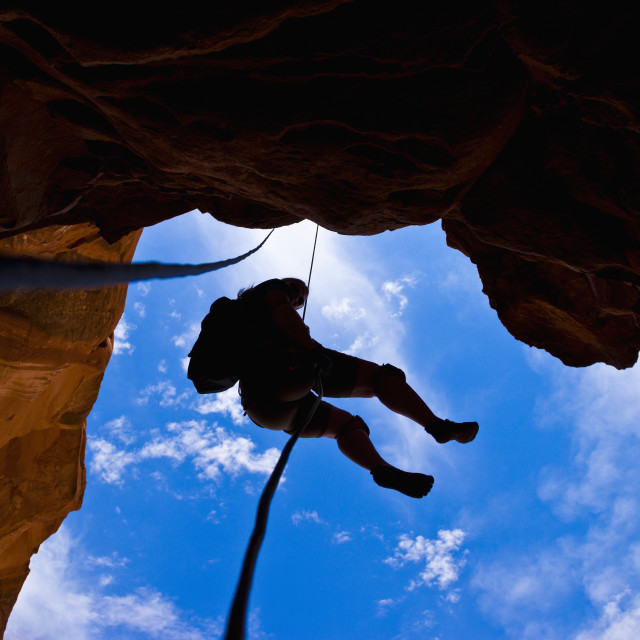 """""""Looking upwards to the silhouette of an adventurer rappelling down a canyon..."""" stock image"""