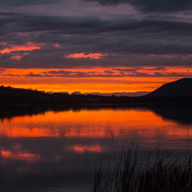 """""""Sunset with vibrant colours reflecting on the tranquil water of Waterloo Lake..."""" stock image"""