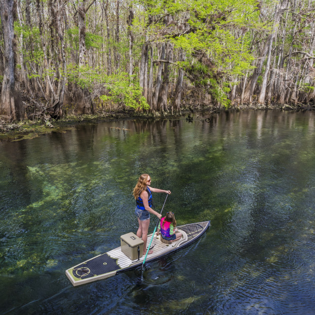 """A mother and daughter paddleboard down the stream of freshwater spring;..."" stock image"