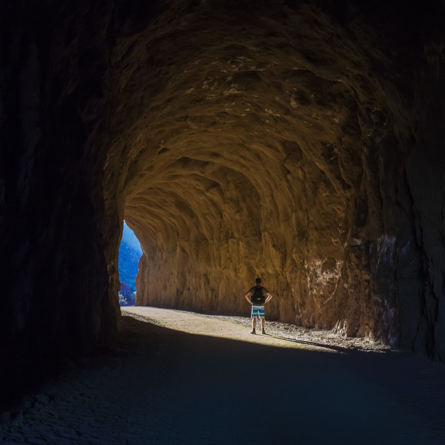 """""""A man hikes through a tunnel in the Nevada spring desert; Boulder City,..."""" stock image"""