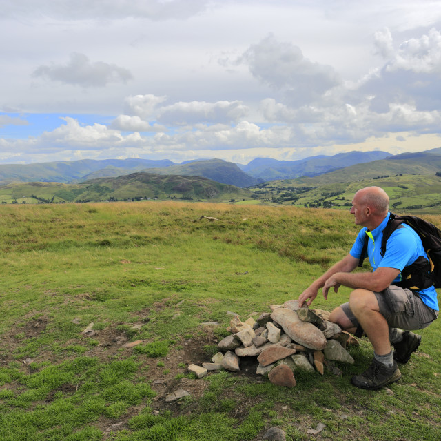 """Walker at the Summit cairn of Great Mell fell, Lake District National Park,..."" stock image"
