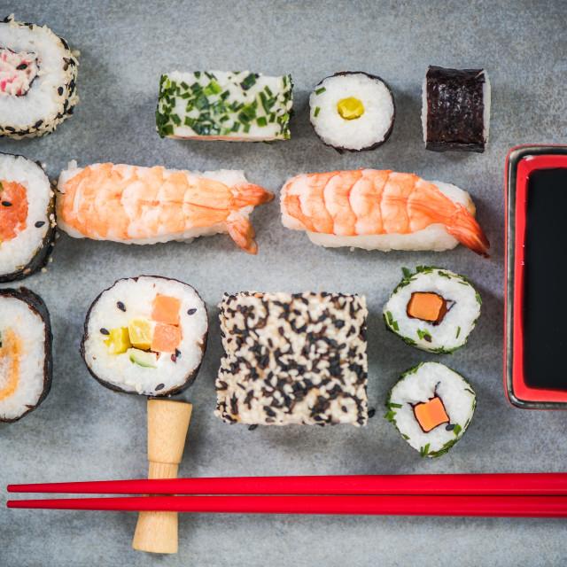 """Sushi on stone or concrete slate with chopsticks"" stock image"