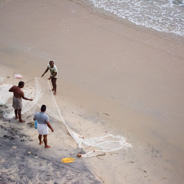 """VARKALA, INDIA - circa FEBRUARY 2017: Three fishermen unfold and clean a..."" stock image"