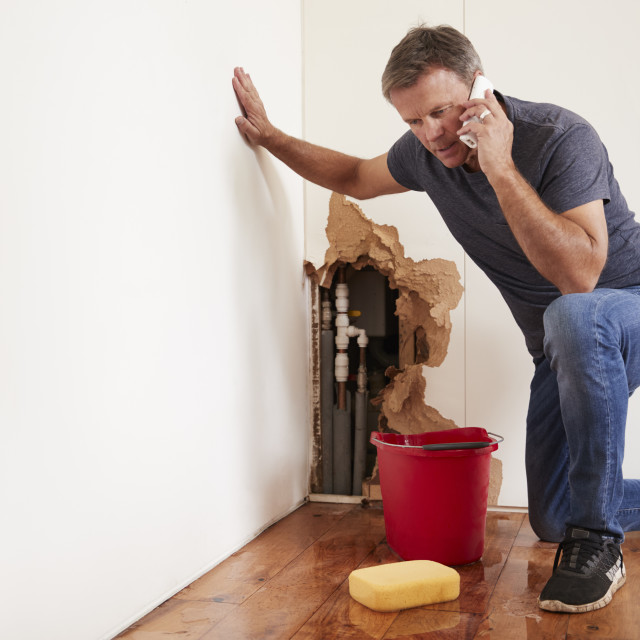 """""""Middle aged man with a burst water pipe phoning for help"""" stock image"""