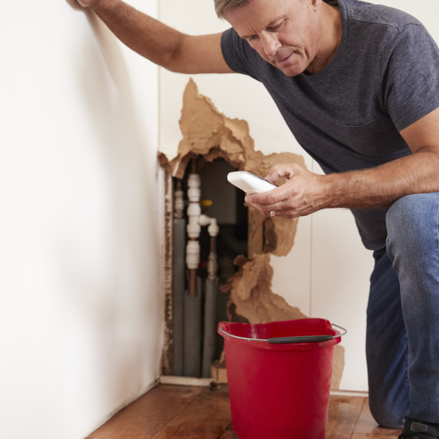 """""""Middle aged man with a burst pipe dialling phone for help"""" stock image"""