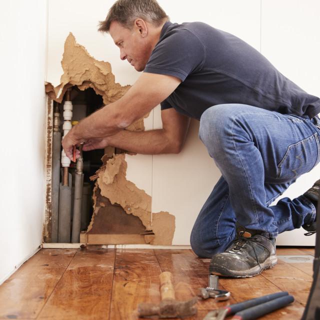 """Middle aged man repairing burst water pipe"" stock image"