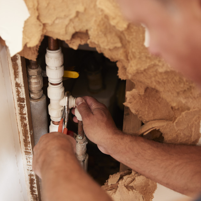 """""""Over shoulder view of middle aged man repairing burst pipe"""" stock image"""