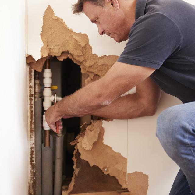 """Middle aged man repairing burst water pipe, vertical"" stock image"