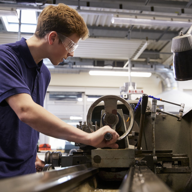 """Male Teenage Apprentice In Engineering Factory Using Lathe"" stock image"