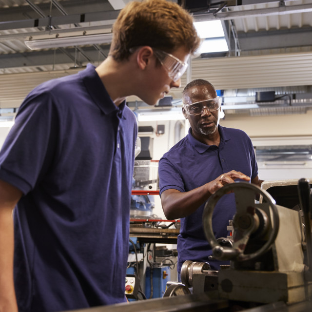 """Engineer Showing Teenage Apprentice How To Use Lathe"" stock image"