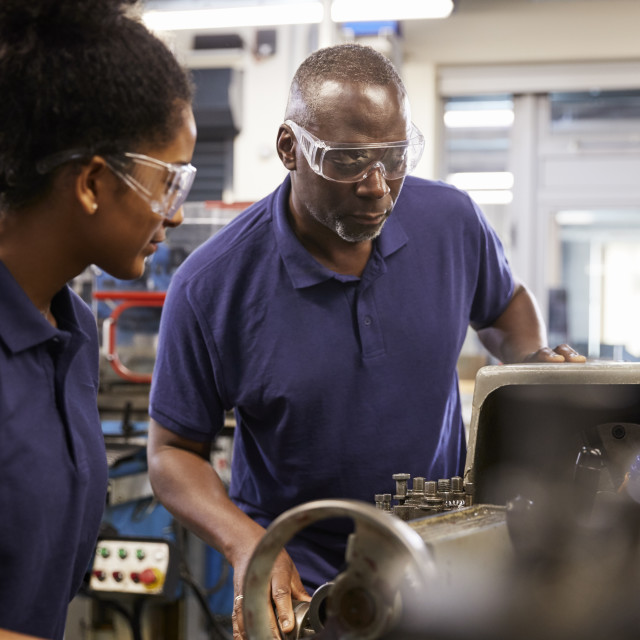 """Engineer Showing Female Teenage Apprentice How To Use Lathe"" stock image"