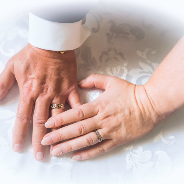 """Hands wearing wedding rings."" stock image"