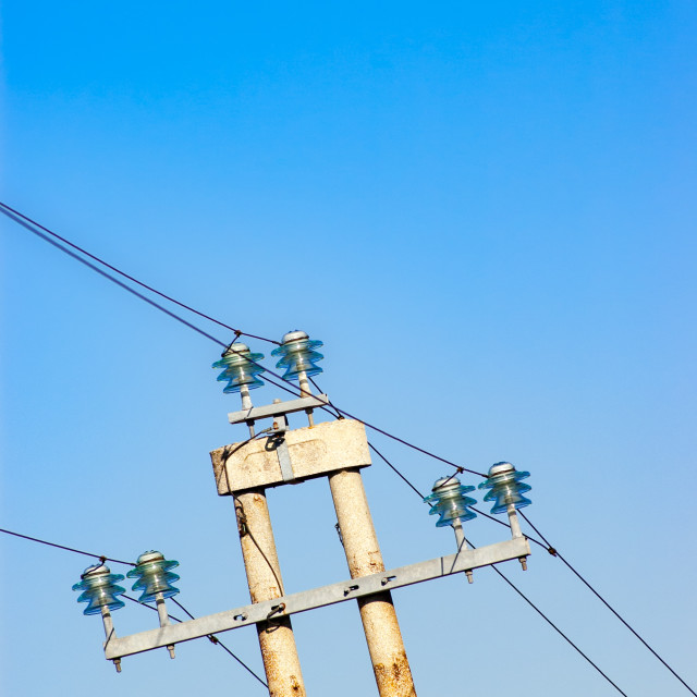 """Electric power line gainst clear blue sky"" stock image"