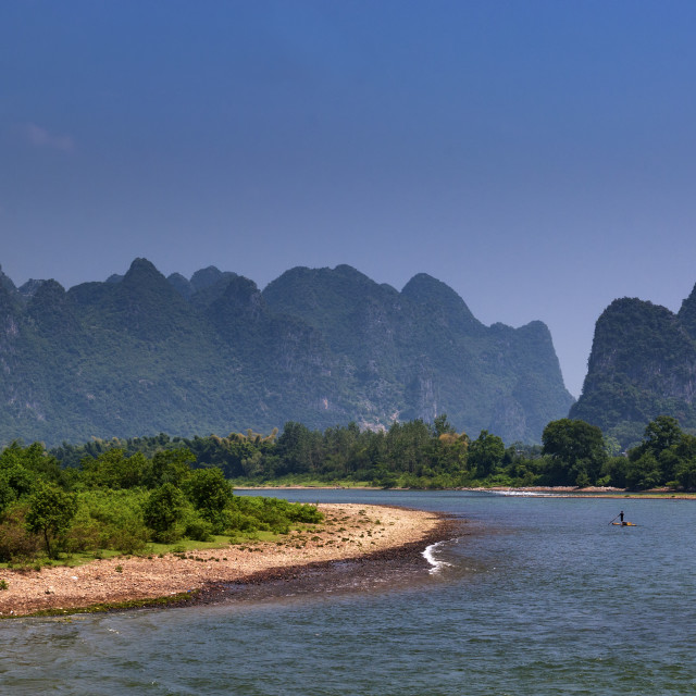 """Yangshuo, China - August 1, 2010: Small raft in the Li River with the tall limestone peaks in the background near Yangshuo in China, Asia."" stock image"