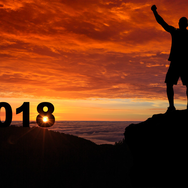 """""""Man silhouette on the mountain top watching the sunrise and 2018"""" stock image"""