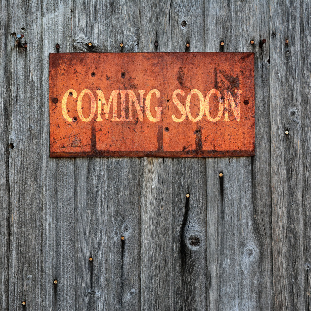 """""""Rusty metal sign with the phrase: Coming soon."""" stock image"""
