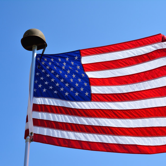 """""""United States flag waving with a military helmet."""" stock image"""