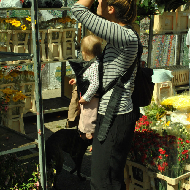 """A woman with child buying flowers at columbia road flower market in east london"" stock image"