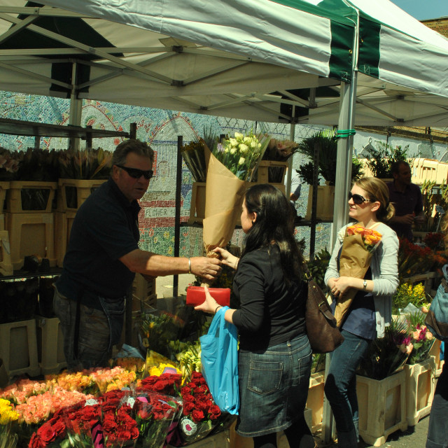 """A woman buying flowers at columbia road flower market in east london"" stock image"
