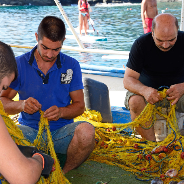 """Cretan fishermen tending to their fishing nets"" stock image"