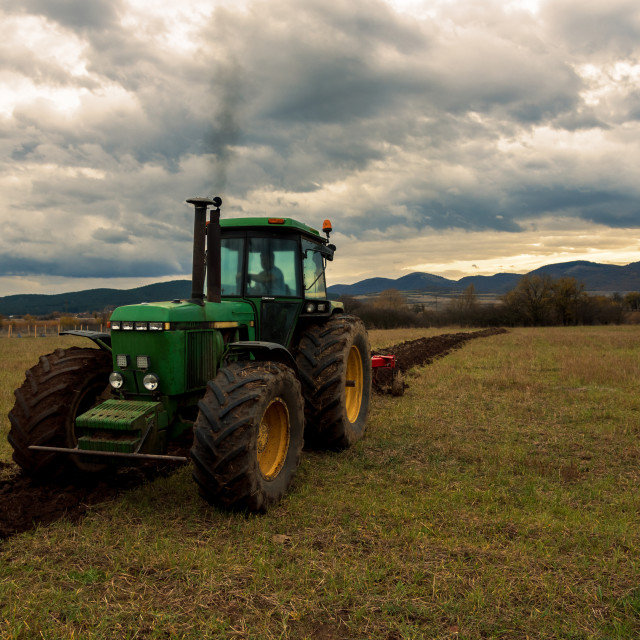 """Tractor plowing fields."" stock image"