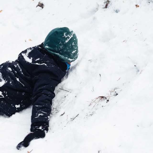 """Young boy having fun with snow in the mountain"" stock image"