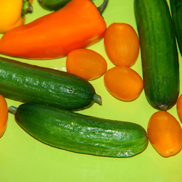 """""""Green, yellow and orange vegetables on green plate"""" stock image"""