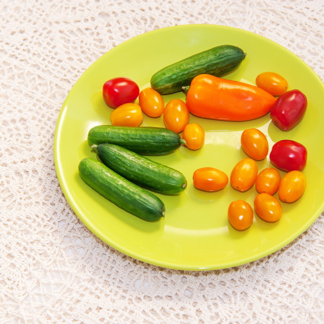 """""""Green plate with mix of colorful vegetables on creamy handmade t"""" stock image"""