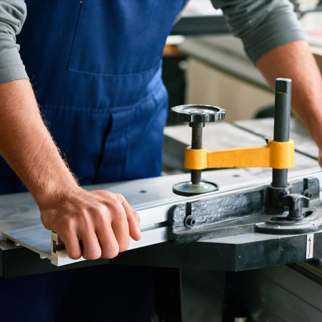 """Closeup of Worker Using Metal Cutting Bench"" stock image"
