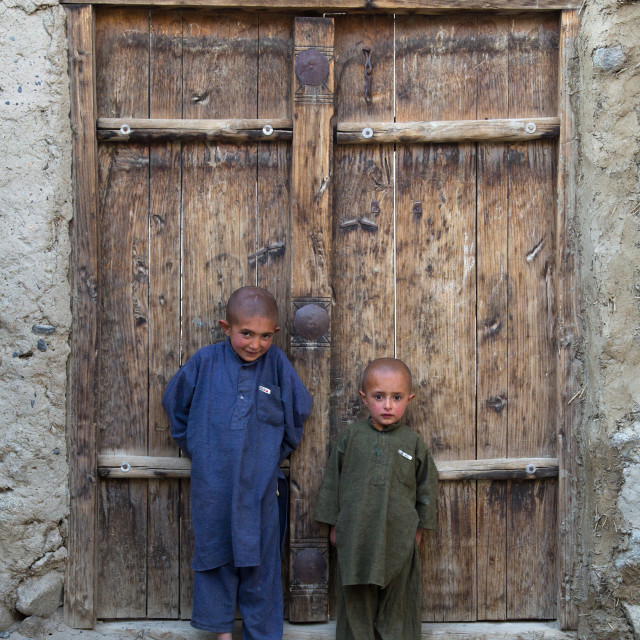 """""""Afghan boys with shaved heads standing in front of a wooden door, Badakhshan..."""" stock image"""