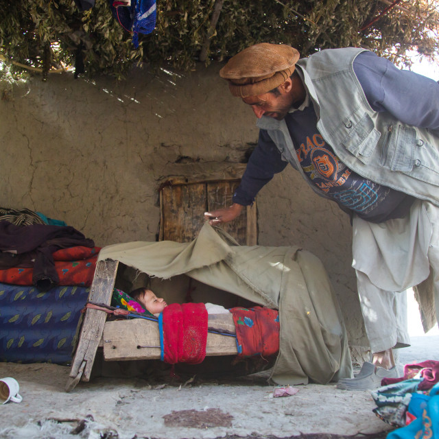 """""""Father looking at his baby sleeping in a craddle, Badakhshan province, Qazi..."""" stock image"""
