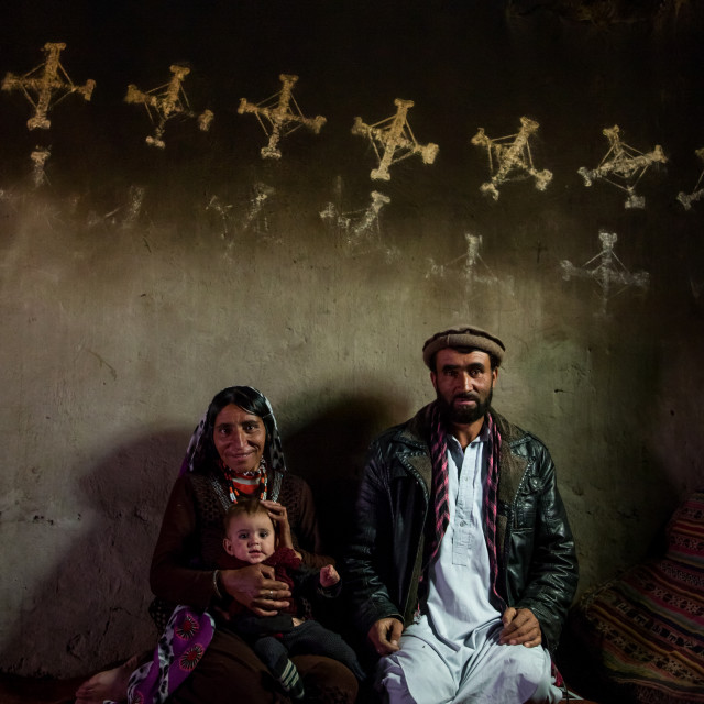 """Afghan family inside their traditional pamiri house with the walls decorated..."" stock image"