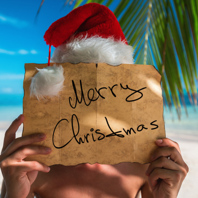 """""""Tourist man with Santa Claus hat relaxing on tropical island bea"""" stock image"""