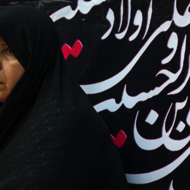 """Iranian shiite woman in front of a billboard with calligraphy during Muharram..."" stock image"