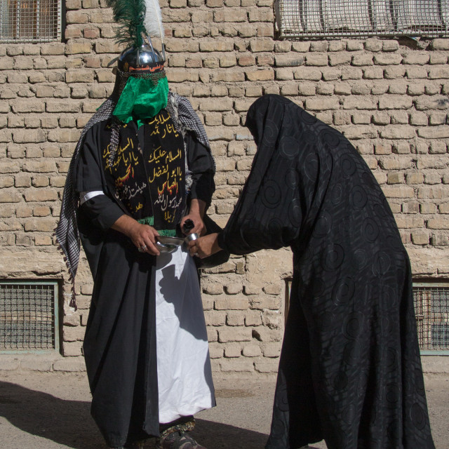 """A Man dressed as Imam Hussein gives water to a woman on Tasua during the..."" stock image"