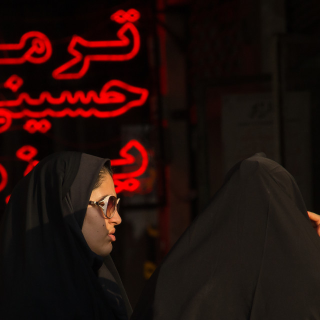 """""""veiled women in front of red neon lights, Central district, Tehran, Iran"""" stock image"""