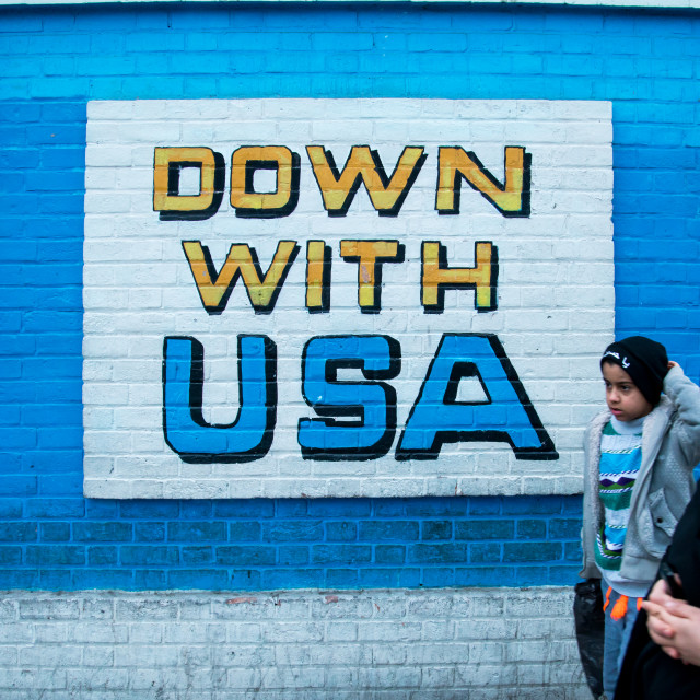"""people passing in front of anti-american mural propoganda on the wall of the..."" stock image"