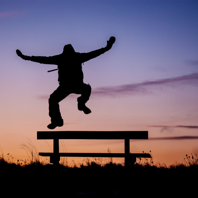 """Jumping silhouette over park bench"" stock image"