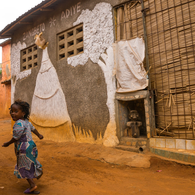 """Benin, West Africa, Porto-Novo, young girl passing in front of zangbeto adiye..."" stock image"