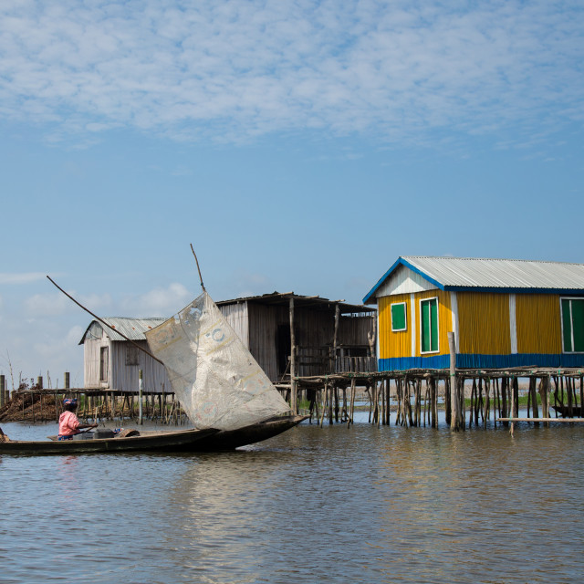 """Benin, West Africa, Ganvié, boat passing in front of the stilt village on..."" stock image"