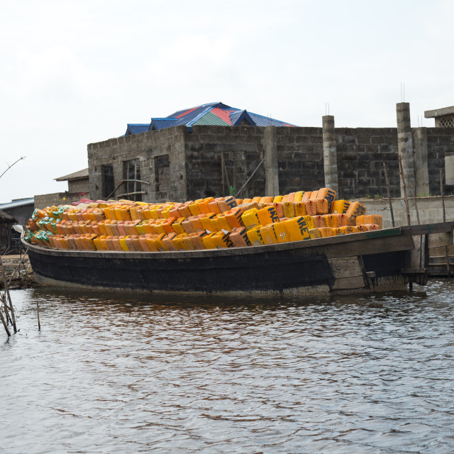 """Benin, West Africa, Ganvié, boat carrying oil jerrycans on lake nokoue"" stock image"