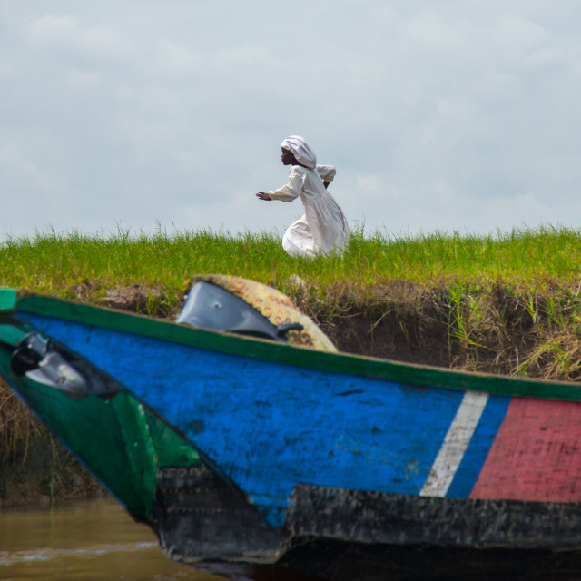 """""""Benin, West Africa, Ganvié, celest church girl running on the bansk of lake..."""" stock image"""