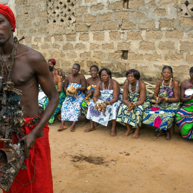 """Benin, West Africa, Bopa, voodoo adept with a red scarf in front of a row of..."" stock image"