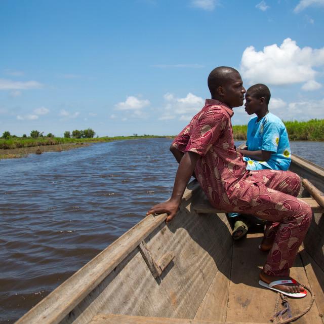"""Benin, West Africa, Ganvié, men on a boat on lake nokoue"" stock image"