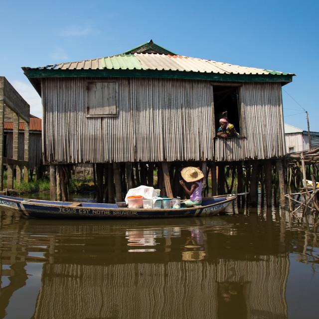 """Benin, West Africa, Ganvié, boat passing in front of the stilt house on lake..."" stock image"