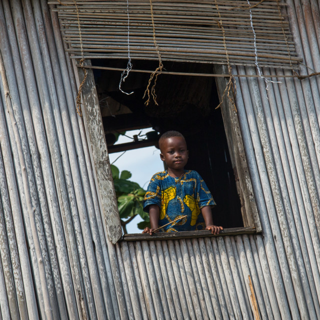 """Benin, West Africa, Ganvié, child looking over a window in a leaning stilt..."" stock image"