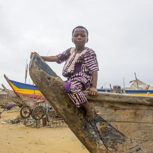 """Benin, West Africa, Cotonou, boy sit on a fishermen boat in the port"" stock image"